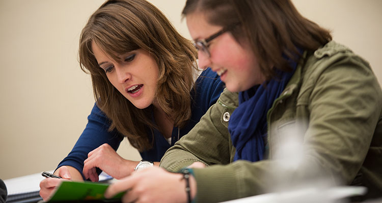 Two students work together on an assignment in an Adult and Community Education classroom.