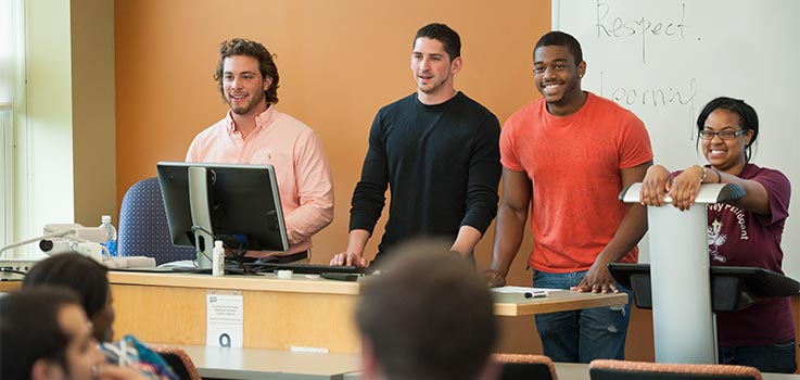 Four students give a presentation at the front of a classroom