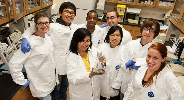 A group of students in lab coats pose for a photo with their professor in a lab