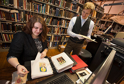 A history student works with historical documents with a staff member in a local museum