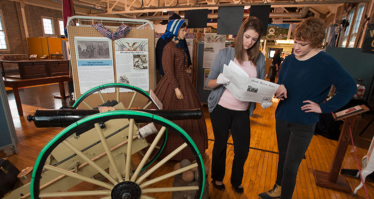 Two students look at documents while standing in a local museum near a small cannon