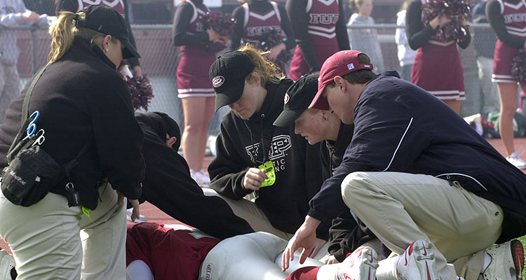 IUP Athletic trainers assess a football player lying prone on the field