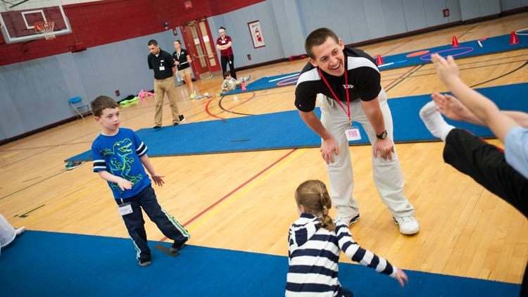Kinesiology students working with children in a gym