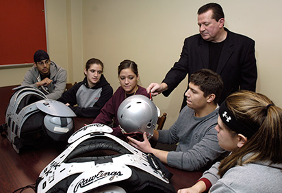 A professor helps students analyze athletic gear