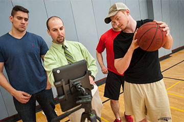 A Kinesiology professor instructs students from a laptop while one holds a basketball
