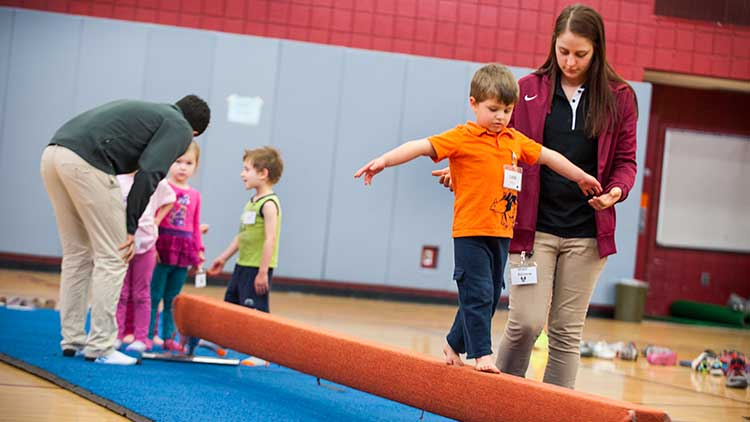 Kinesiology student helping child across balance beam
