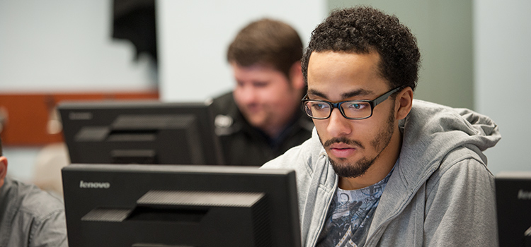 An MIS Student works on a computer during a Management Information Systems class.