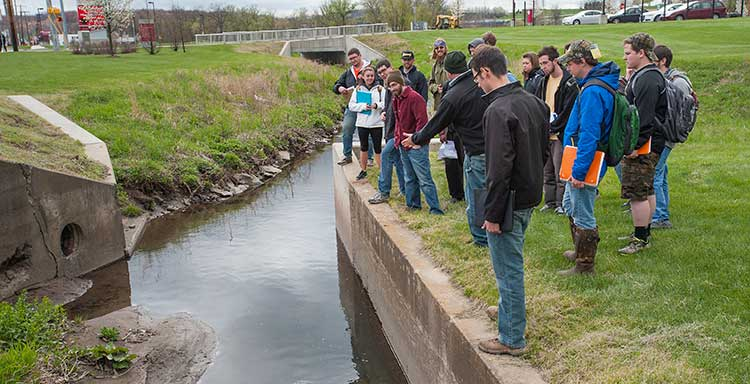 Students stand next to water with professor Richard Hoch