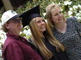 Student posing with parents after Commencement ceremony
