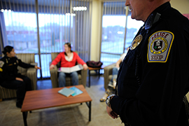 Campus police officer and student talk, while another officer stands in the foreground