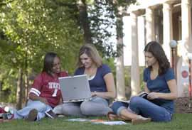 Three students doing school work in the Oak Grove outside of Waller Hall