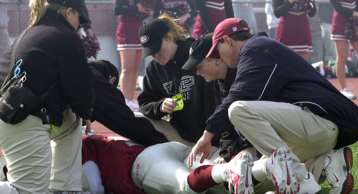 A group of student trainers assist an injured football player during an IUP game
