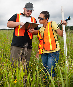 Two students use surveying equipment in a field of tall grass to gather data.
